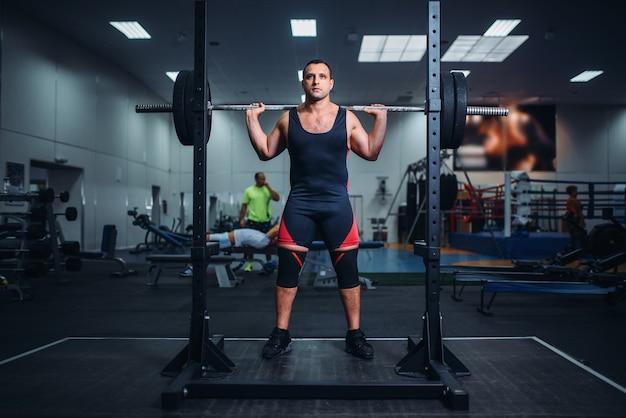 Мускулистый спортсмен готовится сделать приседания со штангой в тренажерном зале. тренировка по тяжелой атлетике, тренировка по пауэрлифтингу
