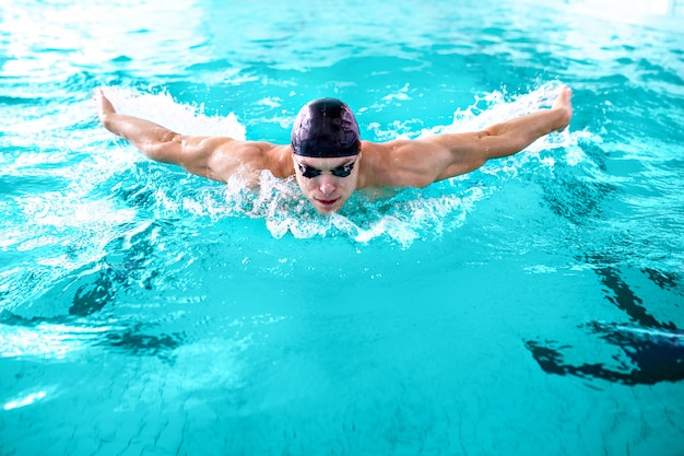Muscular athlete swimming in pool