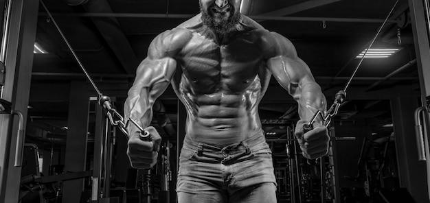 Мускулистый спортсмен тренируется в кроссовере в тренажерном зале. прокачка туловища. концепция фитнеса и бодибилдинга. смешанная техника