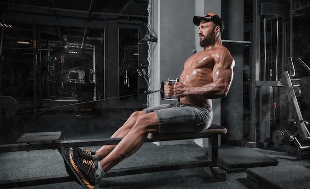 筋肉アスリートはジムでトレーニングします。ブロック内のバックポンピング。フィットネスとボディービルのコンセプト。