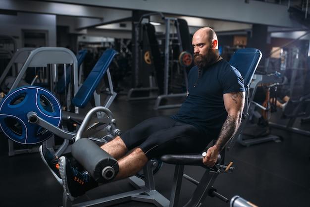 筋肉の運動選手がエクササイズマシンで足を訓練します。
