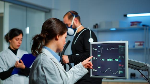 心電図スキャンがコンピューター画面と結果を調べる医師研究者のチームで実行されている間、彼のパフォーマンスを監視するために医療研究所のクロストレーナーで実行されているマスクを持つ筋肉アスリート
