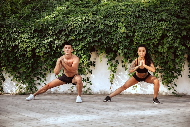 A muscular athletes doing workout at the park. gymnastics, training, fitness workout flexibility. summer city in sunny day on background field. active and healthy lifestyle, youth, bodybuilding.