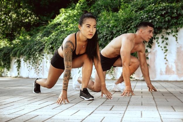 Un atleta muscolare che fa allenamento al parco. ginnastica, allenamento, flessibilità allenamento fitness. città estiva in una giornata di sole sul campo di sfondo. stile di vita attivo e sano, gioventù, bodybuilding.