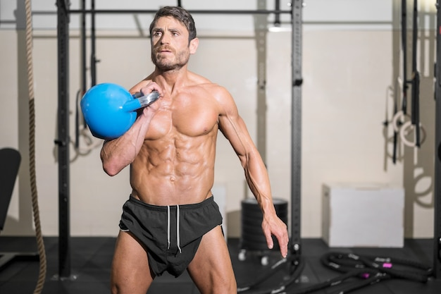 Muscular athletic bodybuilder fitness model posing after exercises in gym