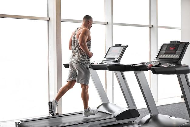 큰 창 근처 디딜 방아 체육관을 실행하는 근육 운동 보디 빌딩 피트니스 모델