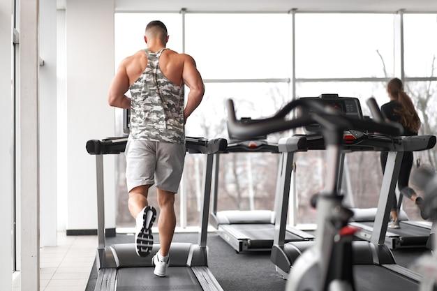 큰 창 근처 디딜 방아 체육관을 실행하는 근육 운동 보디 피트니스 모델