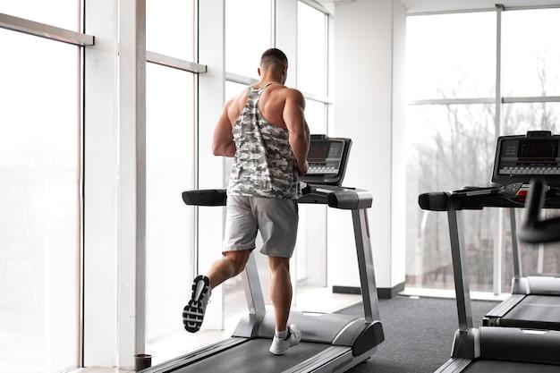 大きな窓の近くでトレッドミルジムを実行している筋肉運動ボディービルダーフィットネスモデル