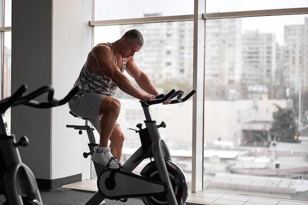 Muscular athletic bodybuilder fitness model sitting stationary bicycle in gym near big window
