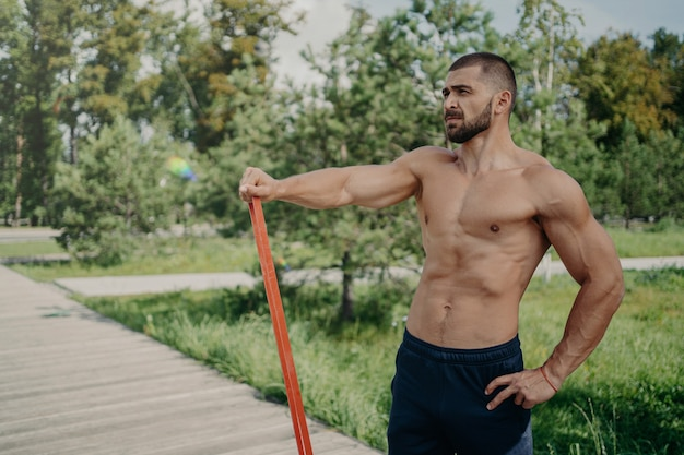 Muscular athletic man has workout with elastic resistance band poses with shirtless muscular body, stands outdoor, concentrated into distance. athlete sportsman has workout in park. healthy lifestyle