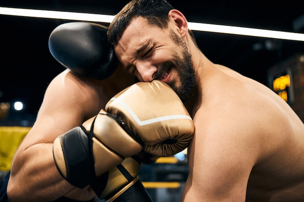 Muscular athletic person getting a painful blow in the jaw with a right hook