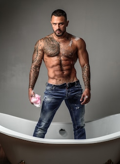 裸の胴体を持つ筋肉の運動セクシーな男性。入れ墨された体を持つ男。自信を持ってハンサムな残忍な男。メンズヘルス。美しい男性の胴体。