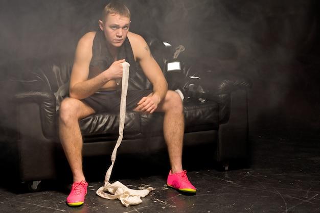 革のソファに座っている煙のような雰囲気の筋肉運動の若いボクサー