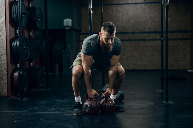 Muscular attractive caucasian bearded man lifting two kettlebells in crossfit gym