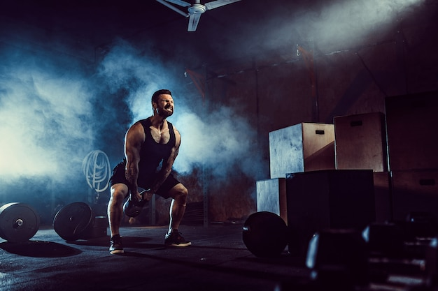 Muscular attractive caucasian bearded man lifting two kettlebells in a gym. weight plates, dumbbell and tires in background.
