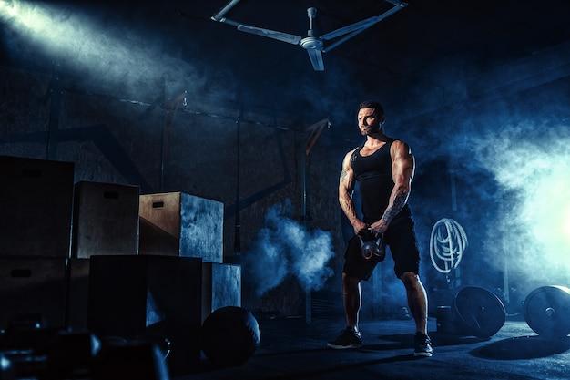 Мускулистый привлекательный кавказский бородатый человек с дегустацией поднимает гирю в тренажерном зале. весовые пластины, гантели и шины в дыму