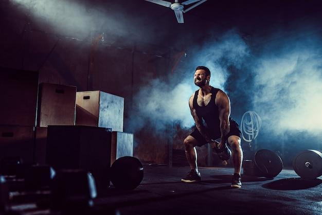 Мускулистый привлекательный кавказский бородатый татуированный мужчина поднимает гирю в тренажерном зале