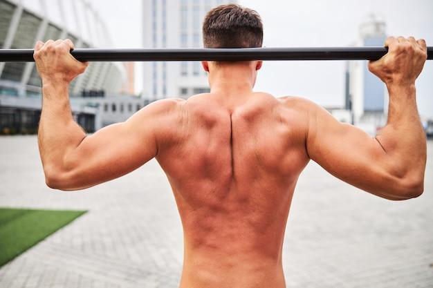 彼が市内中心部の屋外でクロスバーに懸垂をしている間、男性のボディービルダーの筋肉の背中