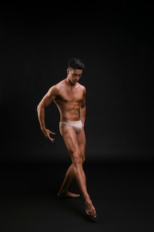 Muscular ballet dancer stretching leg gracefully