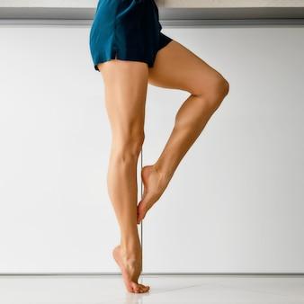 흰색 대리석 배경 위에 프로필에 근육 맨발 여성 다리
