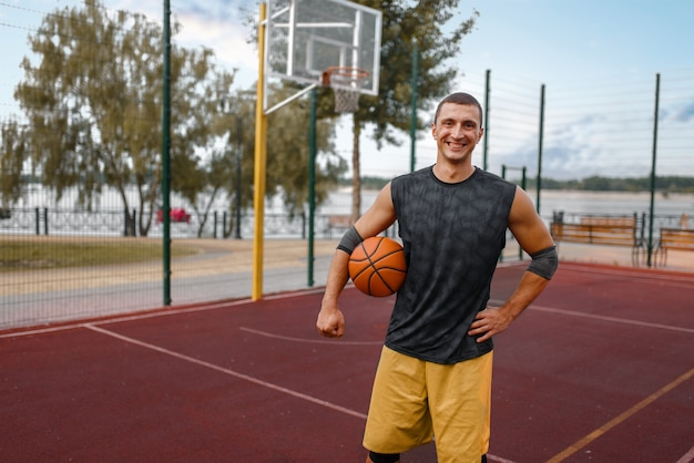 Muscular basketball player on outdoor court.