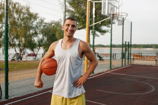 Muscular basketball player on outdoor court