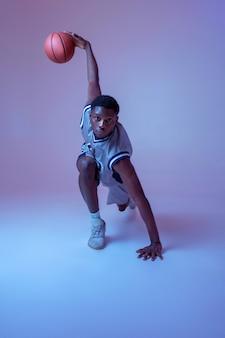 ボールを持った筋肉のバスケットボール選手は彼のスキルを示しています。スポーツゲームをするスポーツウェアのプロの男性バラー、背の高いスポーツマン