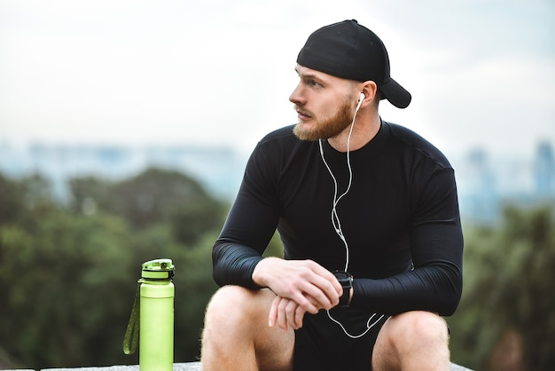 都市公園での良いトレーニングセッションの後、スマートウォッチで燃焼カロリーをチェックする筋肉のひげを生やしたアスリート。