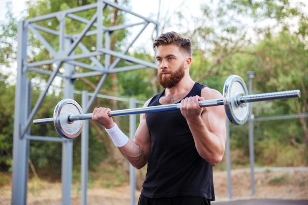Мускулистый бородатый фитнес красавец тренировка со штангой на открытом воздухе