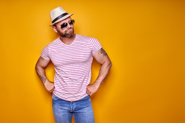 노란색 배경 위에 스튜디오에 서 있는 셔츠 청바지와 세련된 모자 선글라스를 쓴 근육질의 수염 남성