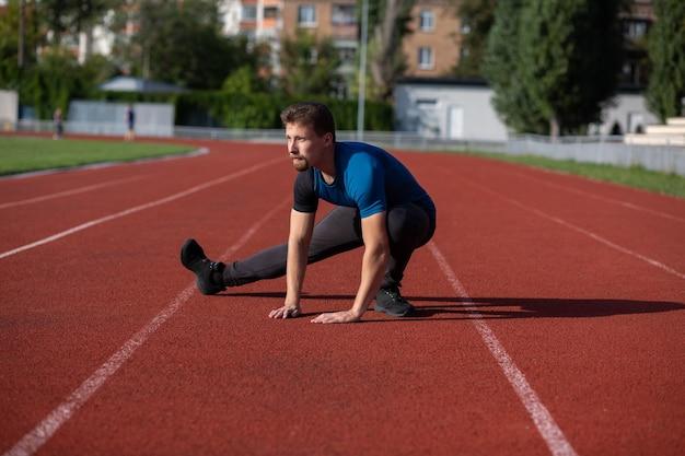 Staduimで走る前に脚のストレッチをしている筋肉のひげを生やした男。空きスペース