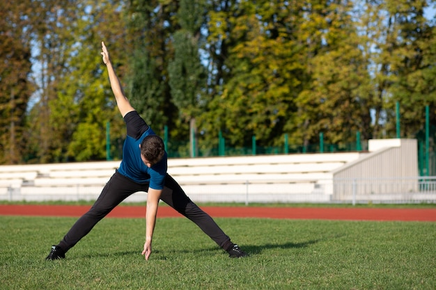 Muscular bearded man doing stretching before workout at the lawn. empty space