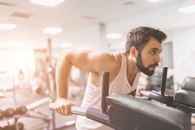 ジムでのトレーニング中の筋肉のひげを生やした男。平行棒でディップをしている白い服を着た集中アスリート男性モデルの肖像画。屋内フィットネス。