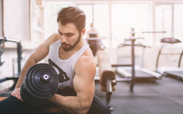 ジムでのトレーニング中の筋肉のひげを生やした男。ダンベルで上腕二頭筋をトレーニングするジムのアスリートの筋肉のボディービルダー。屋内フィットネス。