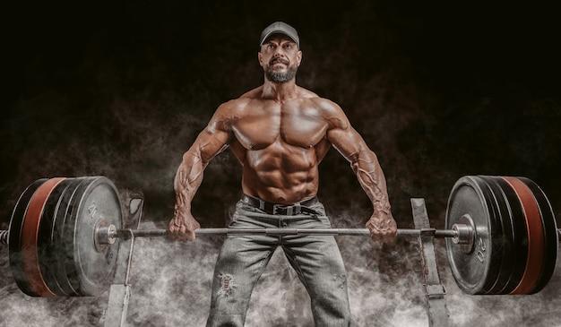 Мускулистый бородатый мужчина поднимает штангу. бодибилдинг, фитнес, концепция пауэрлифтинга.