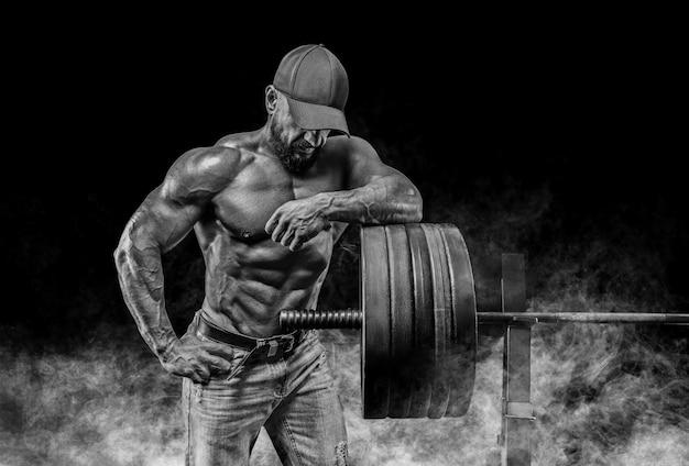 Мускулистый бородатый мужчина стоит возле штанги. бодибилдинг, фитнес, концепция пауэрлифтинга.