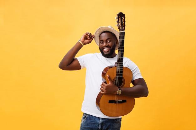 근육 질의 흑인 남자 기타 연주, 청바지와 흰색 탱크 탑을 입고.