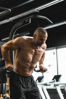 체육관에서 운동하는 동안 삼두근과 가슴 근육을 위한 딥스를 하는 근육질 보디빌더