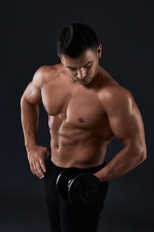 Muscular bodybuilder doing exercises with dumbbell over black .strong athletic man shows body,abdominal muscles,biceps and triceps.work out,gaining weight,pumping up muscles with dumbbells.