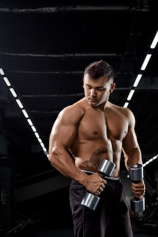 Muscular bodybuilder doing exercises with dumbbell in gym.strong athletic man shows body,abdominal muscles,biceps and triceps.work out,gaining weight,pumping up muscles with dumbbells.
