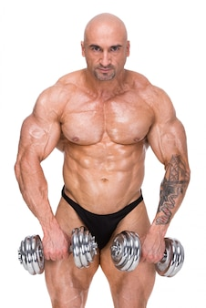 Muscular bodybuilder exercising with two weights.