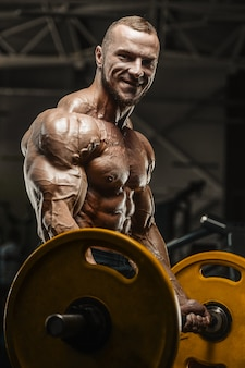 Muscular bodybuilder fitness man doing arms exercises in gym