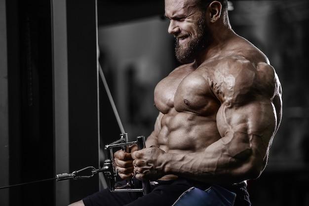 ジムの裸の胴体でプルアップ運動を行う筋肉ボディービルダーフィットネス男性。背中の筋肉トレーニングフィットネスとボディービルの概念の背景を汲み上げるハンサムな強い運動男性。
