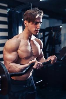 체육관에서 큰 아령으로 팔뚝에 운동을하는 근육 보디 사람