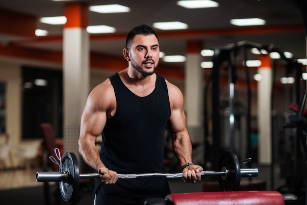 Muscular bodybuilder guy doing exercises with a barbell.