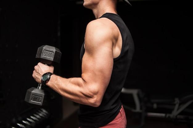 黒の背景の上でダンベルと練習をしている筋肉のボディービルダーの男