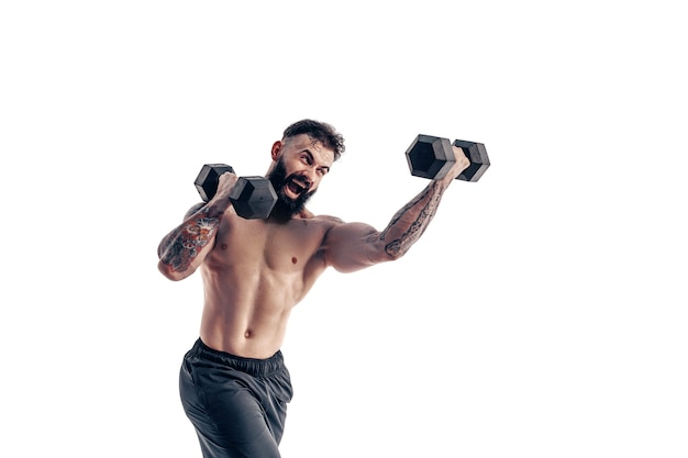Мускулистый парень культурист делает упражнения с гантелями над ничуть