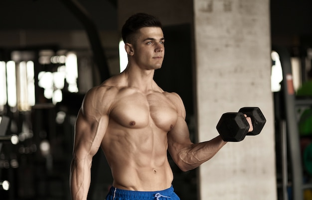 ジムでダンベルで演習を行って筋肉ボディービルダー男