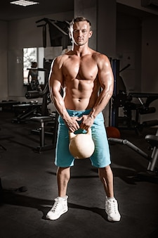 ジムで体重と演習を行う筋肉ボディービルダー男
