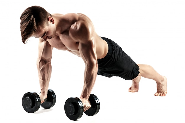 Muscular bodybuilder guy doing push-ups on dumbbells from the floor over white background